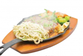Fish and vegetables served sizzling on a hot plate poured with mushroom sauce on top