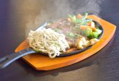 Chicken and vegetables served sizzling on a hot plate poured with mushroom sauce on top.