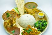 Nepali Traditional thali served with rice, daal( lentil), mix veg curry, , Sauteed spinach( Saag), Pappadum, Salad, pickle and Ghee.